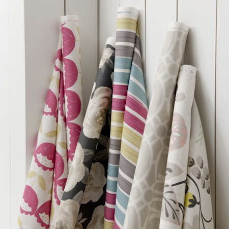 Clarke and Clarke -  Folia Fabric Collection - Rolls of fabric in grey and white, coloured stripes, dark grey and cream florals, and stylised florals in pink and green and grey and cream