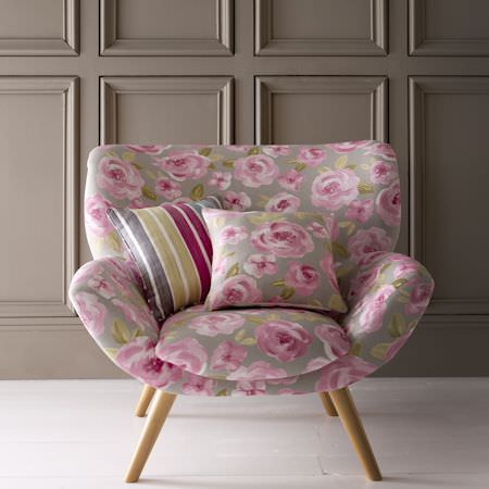 Clarke and Clarke -  Folia Fabric Collection - Wide, rounded armchair covered in grey fabric with large pink roses and green leaves, with a matching cushion and a coloured striped cushion