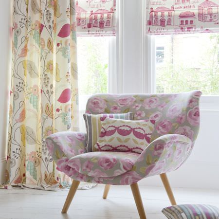 Clarke and Clarke -  Folia Fabric Collection - Grey, pink and green floral armchair with pink and cream house print fabric, multicoloured leaf print curtains, and patterned cushions