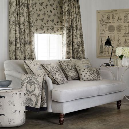 Clarke and Clarke -  Fougeres Fabric Collection - White sofa, white and grey patterned cushions and curtains, a round dog print footstool, and butterfly print blinds
