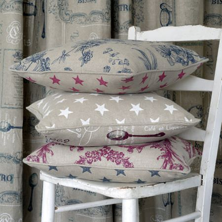 Clarke and Clarke -  Fougeres Fabric Collection - A stack of 3 grey, navy, pink and white patterned and star print cushions on a white wooden chair, with patterned curtains