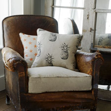 Clarke and Clarke -  Fougeres Fabric Collection - Distressed brown leather armchair with an ivory seat cushion, and two star and stag print cushions in white, orange and grey