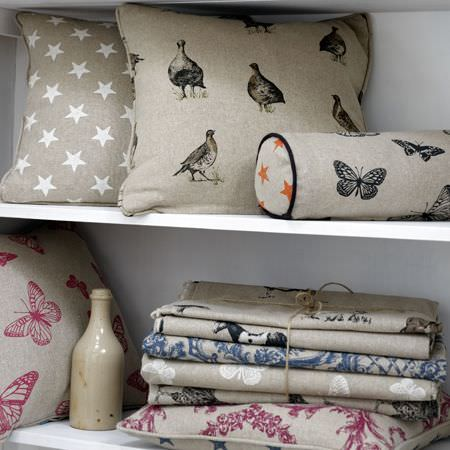 Clarke and Clarke -  Fougeres Fabric Collection - Muted shades of grey, pink and blue making up star, butterfly, bird and floral fabrics in a pile and on cushions