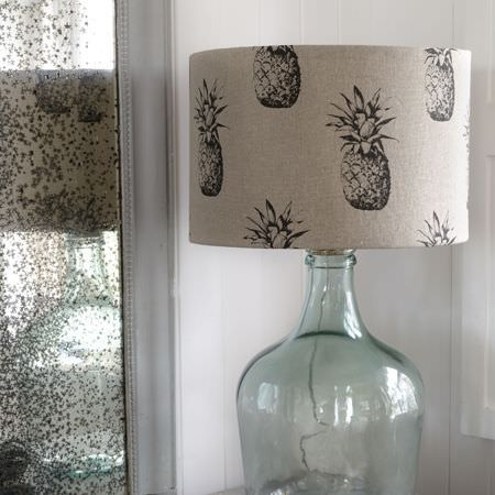 Clarke and Clarke -  Fougeres Fabric Collection - A clear, large, bottle shaped lamp with a large shade made in off-white, featuring a repeated dark grey pineapple print