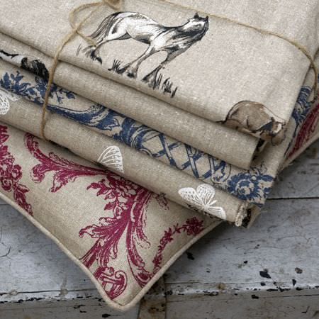 Clarke and Clarke -  Fougeres Fabric Collection - A grey and dark pink patterned cushion under a tied pile of four grey, white and navy horse and butterfly print fabrics