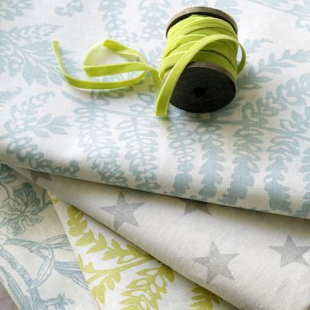Clarke and Clarke -  Fougeres Fabric Collection - A reel of lime green velour ribbon atop four folds of pale blue, grey, green and white star print and patterned fabrics