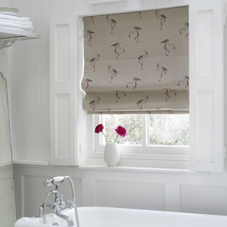 Clarke and Clarke -  Fougeres Fabric Collection - A pale grey window blind with a heron print pattern, hanging in a bright white bathroom with a white vase and pink flower