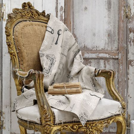 Clarke and Clarke -  Fougeres Fabric Collection - An ornately carved, distressed gold framed armchair with a beige seat and back, and a swathe of grey and white fabric