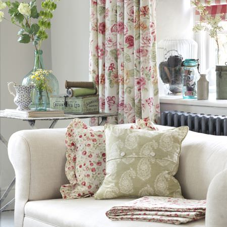 Clarke and Clarke -  Genevieve Fabric Collection - Frilly floral cushion and fabric, coordinating curtains, a green and white paisley cushion, with cream sofa, folding table, and glass vases