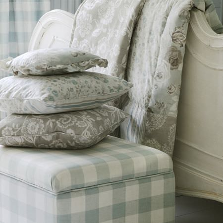 Clarke and Clarke -  Genevieve Fabric Collection - Blue-grey and white checked fabric-covered storage block, with grey and white floral cushions and fabric, and an ornate white wood bedframe