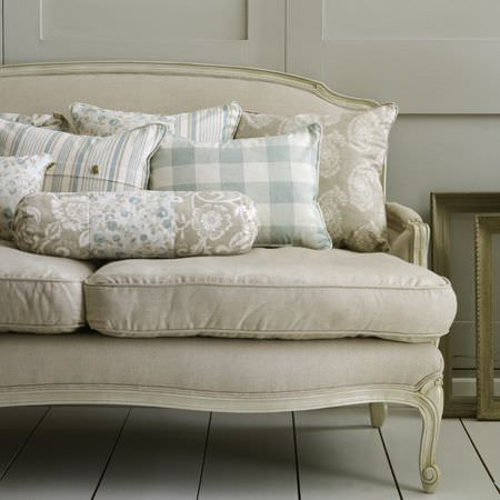 Clarke and Clarke -  Genevieve Fabric Collection - Off-white sofa with shabby chic cream wood edges, grey and cream patterned cushions, and blue and white checked and striped scatter cushions