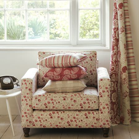 Clarke and Clarke -  Genevieve Fabric Collection - Square armchair with small red flowers, stack of 3 different red and cream cushions, rolls of matching fabric, white side table with phone