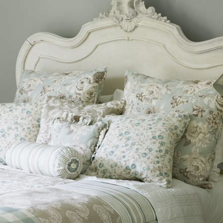 Clarke and Clarke -  Genevieve Fabric Collection - Ornate cream headboard with cream, blue and grey patterned bedding and a selection of matching floral scatter cushions, and bolster cushion