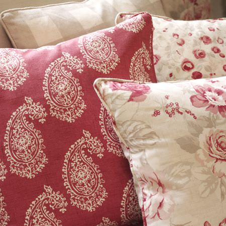 Clarke and Clarke -  Genevieve Fabric Collection - Red cushion with white paisley pattern, cream cushions with different red floral prints, and a beige and cream checked cushion