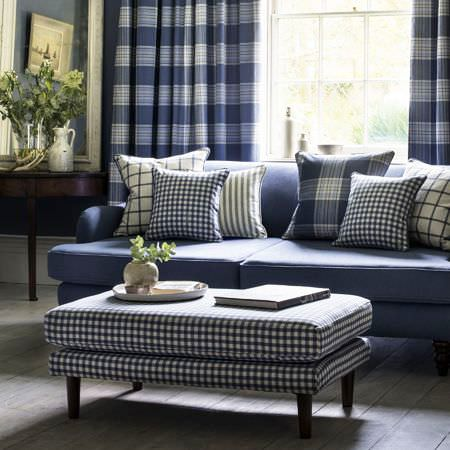 Clarke and Clarke -  Glenmore Fabric Collection - Plain blue sofa, upholstered coffee table with chequered design in blue and matching blue curtains