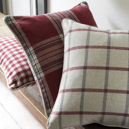 Clarke and Clarke -  Glenmore Fabric Collection - White cushion with red and grey plaid pattern, red cushion with a plaid design and white cushion with chequered pattern