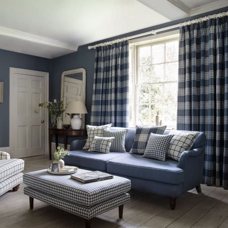 Clarke and Clarke -  Glenmore Fabric Collection - Blue sofa covered with chequered or striped cushions, white armchair with blue plaid pattern and matching curtains