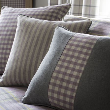 Clarke and Clarke -  Glenmore Fabric Collection - Grey cushion with purple chequered pattern in the middle, and beige cushions with purple stripe or square pattern