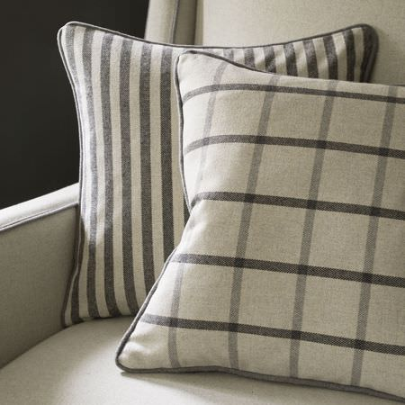 Clarke and Clarke -  Glenmore Fabric Collection - Close-up view of a beige cushion with grey stripes and a beige cushion featuring grey plaid pattern