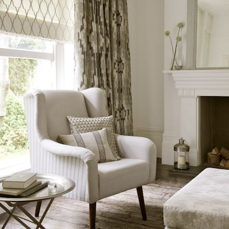 Clarke and Clarke -  Global Luxe Fabric Collection - Plain and striped cream armchair with striped and patterned cushions, cream floral footstool, cream and brown patterned blind and curtains