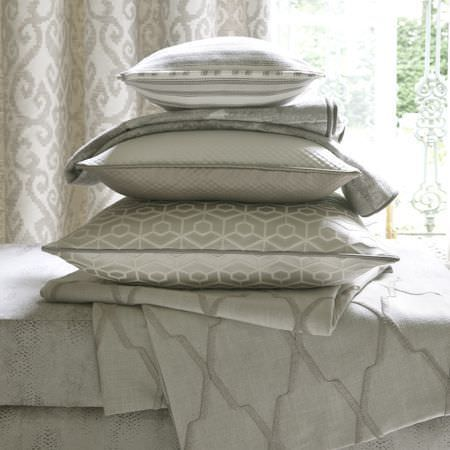 Clarke and Clarke -  Global Luxe Fabric Collection - Stack of grey and cream patterned cushions and fabrics on a grey dotted base, with cream and grey-brown curtains behind