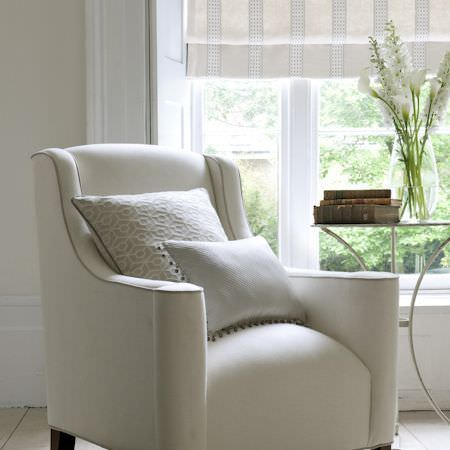 Clarke and Clarke -  Global Luxe Fabric Collection - Cream armchair with smooth lines, one patterned and one fringed cushion, cream striped blinds, a simple metal table and a large glass vase
