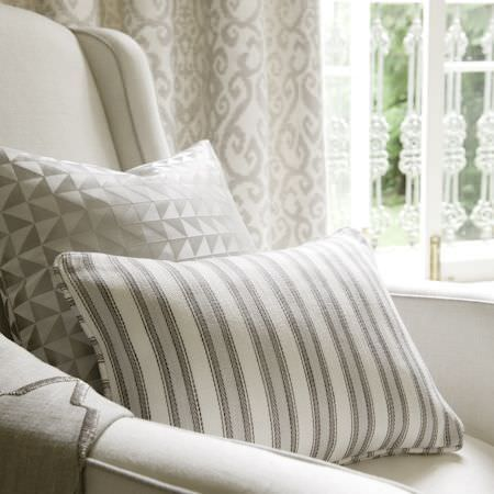 Clarke and Clarke -  Global Luxe Fabric Collection - Cushion with white, grey and grey-blue stripes, with a square cushion with rows of cream and grey-brown triangles, on an off-white armchair