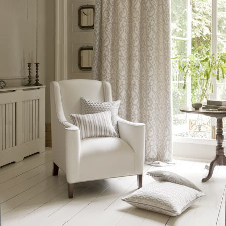 Clarke and Clarke -  Global Luxe Fabric Collection - Elegant white armchair with cushions featuring stripes, patterns and beaded fringes with patterned curtains and a 3-legged carved wood table