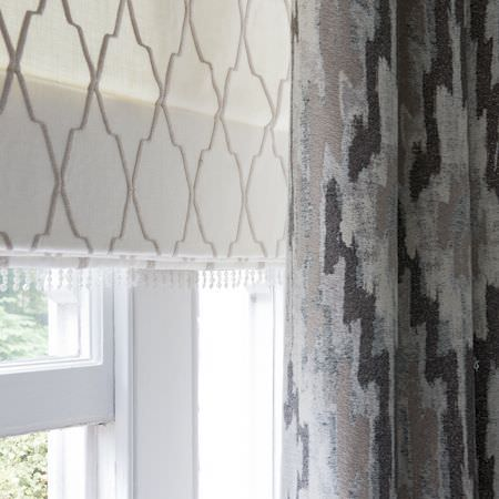 Clarke and Clarke -  Global Luxe Fabric Collection - Thin cream blinds with brown lines creating a geometric design, and grey curtains with a black and brown African style zigzag pattern