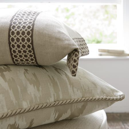 Clarke and Clarke -  Global Luxe Fabric Collection - Cream and brown crocheted stripes on a cream cushion, above another cushion with a camo print in various shades of cream