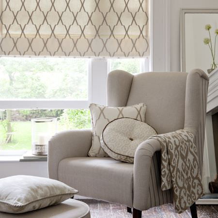 Clarke and Clarke -  Global Luxe Fabric Collection - Stone coloured armchair with striped sides and round footstool, three patterned cream cushions, matching blinds, and cream and brown fabric