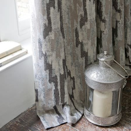 Clarke and Clarke -  Global Luxe Fabric Collection - African style stone-effect grey, beige and brown geometric print curtains, with cream candle in an embossed silver and glass lantern