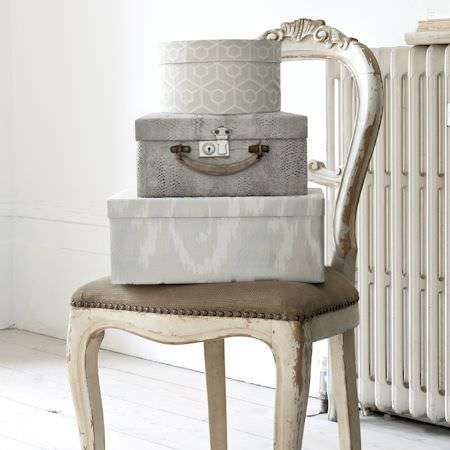 Clarke and Clarke -  Global Luxe Fabric Collection - Shabby chic open back carved wooden chair with padded seat, stacked with three grey patterned boxes and travel cases