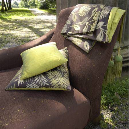Clarke and Clarke -  Grand Palais Fabric Collection - Green leaf and flower patterned cushions and fabrics on a brown upholstered chair