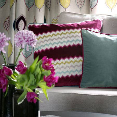 Clarke and Clarke -  Gustavo Fabric Collection - Leaf patterned curtains, witha light blue cushion, and a violet, green, grey, white and blue zigzag patterned cushion