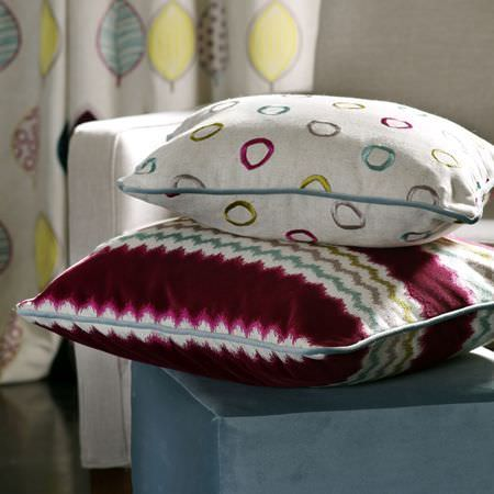 Clarke and Clarke -  Gustavo Fabric Collection - Mulberry, blue, green, grey and white zigzag and circle prints on two cushions, on a light blue footstool, with a white sofa