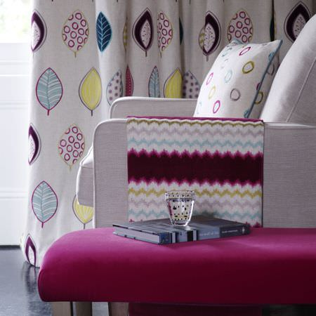 Clarke and Clarke -  Gustavo Fabric Collection - A fuschia bench, a white sofa, with mulberry, grey, blue and green patternedthrows, cushions and leaf print curtains