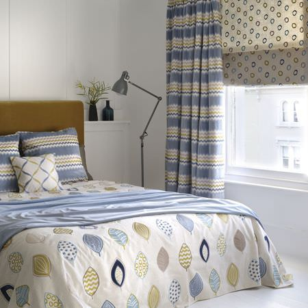 Clarke and Clarke -  Gustavo Fabric Collection - Blue, beige and white fabrics making up leaf print bedding, zigzag curtains and cushions, with a blind, a lamp and a throw