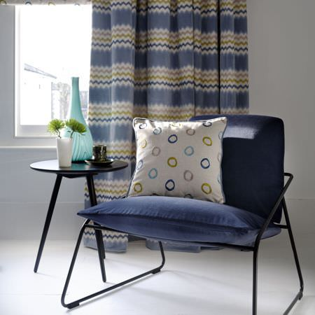 Clarke and Clarke -  Gustavo Fabric Collection - Black framed navy cushioned seat, withdark blue, grey, green and white circle and zigzag patterned curtains and a cushion