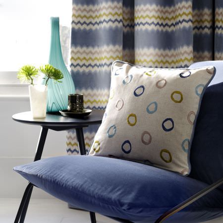 Clarke and Clarke -  Gustavo Fabric Collection - A black table beside a chair with navy seat and back cushions, a circle print scatter cushion, and zigzag print curtains
