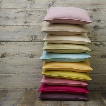 Clarke and Clarke -  Henley Fabric Collection - A stack of cushions in plain shades of purple, hot pink, dusky pink, lime, yellow, blue, green, cream, beige and baby pink