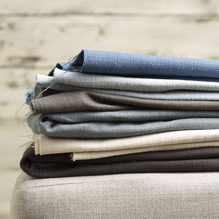 Clarke and Clarke -  Henley Fabric Collection - Folds of plain fabrics in light and dark shades of blue, grey and cream lying on a plain off-white coloured seat cushion
