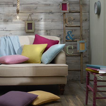 Clarke and Clarke -  Henley Fabric Collection - Plain, bright scatter cushions on a beige sofa, beside a ladder, a purple stool, letters and picture frames and a clock