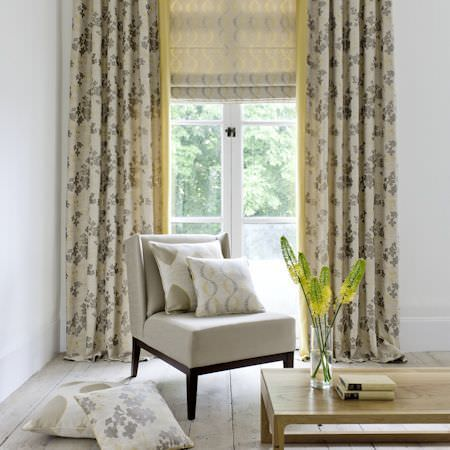 Clarke and Clarke -  Holland Park Fabric Collection - Low wood coffee table with glass vase, plain cream chair, four cream and grey patterned cushions, matching floral curtains, and cream blind