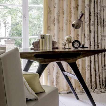 Clarke and Clarke -  Holland Park Fabric Collection - Sleek dark wood table with pewter desk lamp, cream and gold-grey floral curtains, and a cream chair with scatter cushions