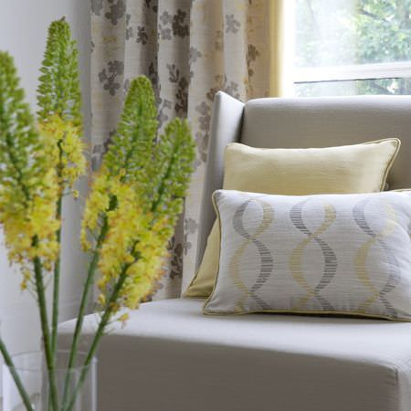 Clarke and Clarke -  Holland Park Fabric Collection - Putty coloured chair with square pale yellow cushion, patterned yellow, grey and cream rectangular cushion, floral grey and cream curtains