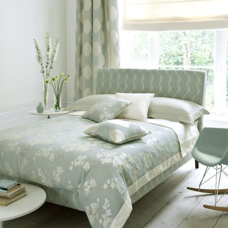 Clarke and Clarke -  Holland Park Fabric Collection - Duck egg blue bed and chair, with white pillows, blue and white patterned cushions and curtains, and blue and white floral bedding