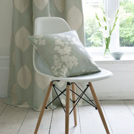 Clarke and Clarke -  Holland Park Fabric Collection - Light blue and white floral cushion on a white plastic chair with wooden legs, with duck egg blue and white leaf print curtains