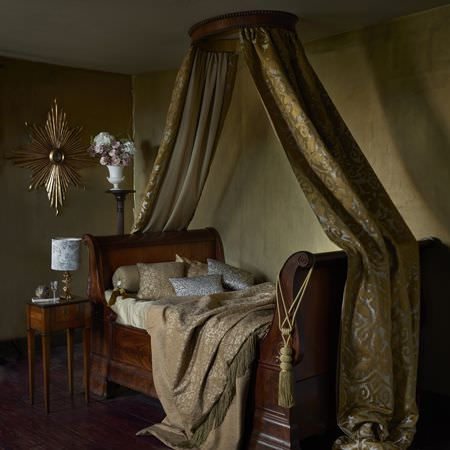 Clarke and Clarke -  Imperiale Fabric Collection - Vintage wooden bed covered with soft luxurious fabrics matching with an elegant bed canopy in gold