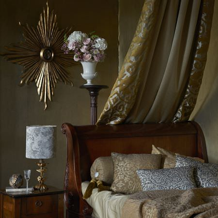 Clarke and Clarke -  Imperiale Fabric Collection - A close-up view of luxurious cushions in gold and silver and a bed canopy featuring gold velvet design